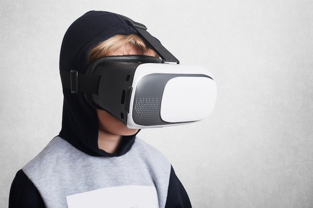 Small boy wears virtual reality glasses, sees something amazed, poses against white wall. children, modern technology and entertainment concept. child uses vr mobile game application