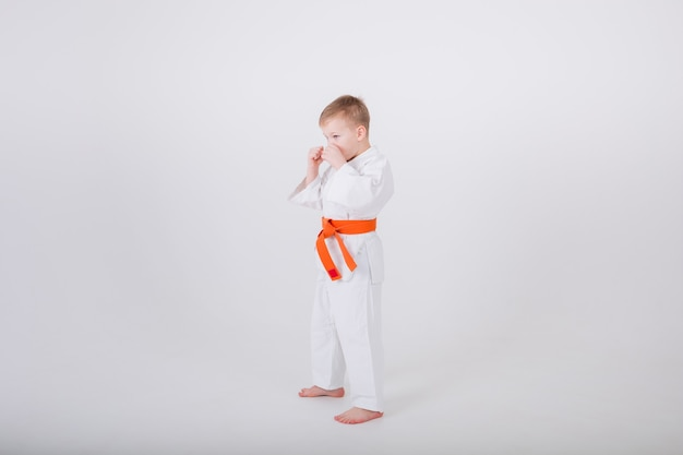Small boy in a white kimono with an orange belt stands sideways in a protective pose against a white wall with a copy of the space
