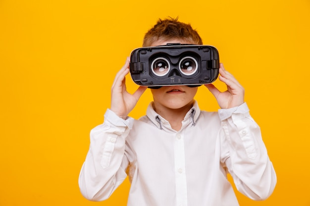 Small boy in white shirt looking at camera through virtual reality headset isolated