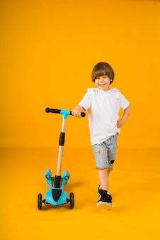 Small boy in a white t-shirt and denim shorts stands and holds a scooter on a yellow surface with space for text. sports for children