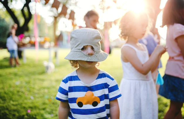 Small boy with friends standing outdoors on garden party in summer, hole in his hat. celebration concept.