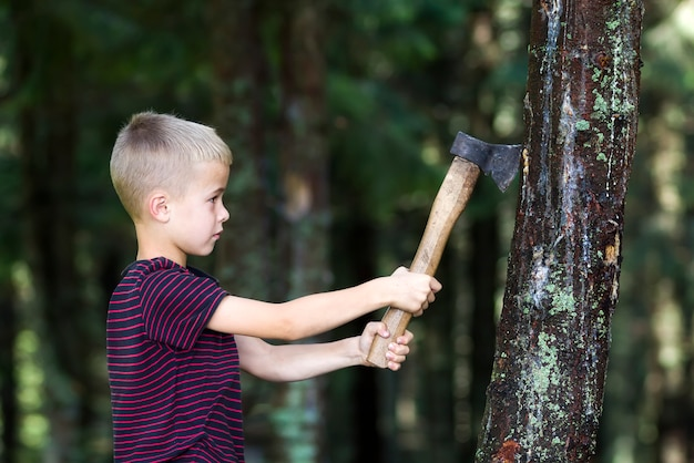 Small boy with heavy old iron axe cutting tree trump in forest on summer day. outdoor activities and physical labor.