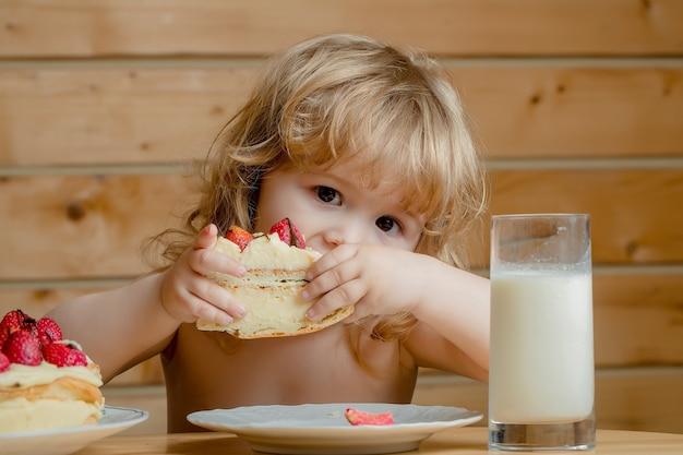 Small boy with strawberry cake and yogurt