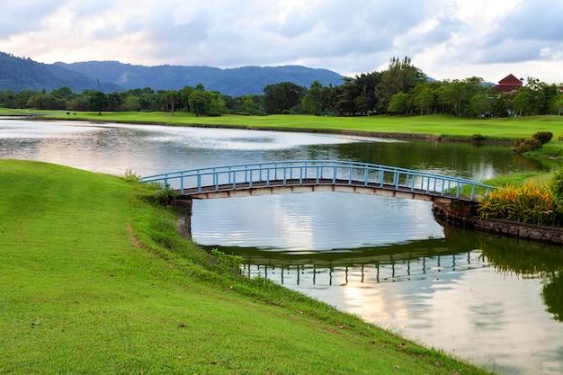 ゴルフ場の緑の芝生とラグーンの小さな橋。