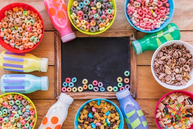 Small bright cereals on chalkboard on wooden table