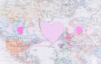 Small bright paper hearts on world map