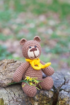 A small brown bear with a yellow scarf. knitted toy, handmade, amigurumi