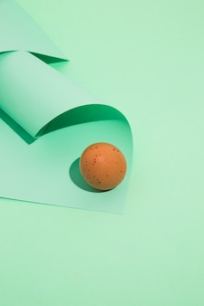 Small brown chicken egg with rolled paper on green table