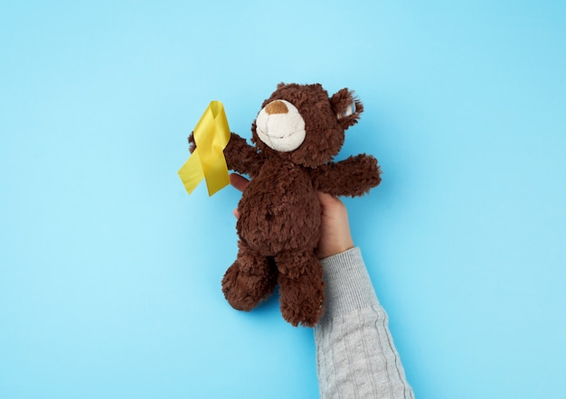 Small brown teddy bear which holds in its paw a yellow ribbon folded in a loop
