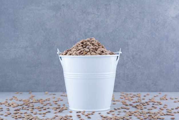 Small bucket of brown lentil sitting in the midst of scattered grains on marble surface