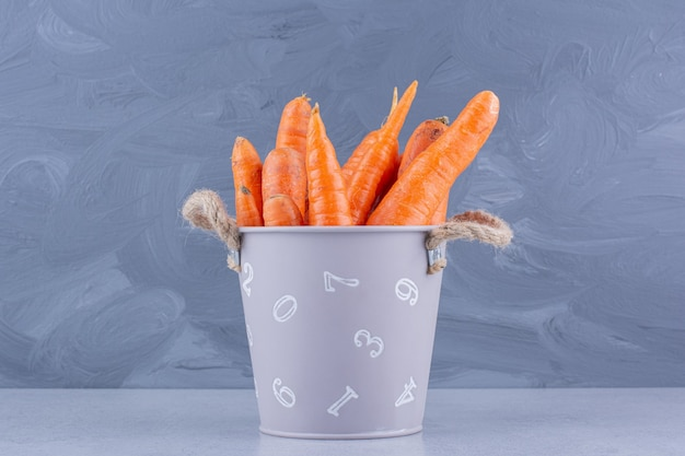 Small bucket of carrots on marble background.