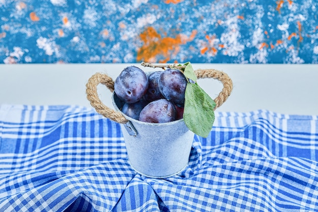 Small bucket of garden plums on a blue tablecloth. high quality photo