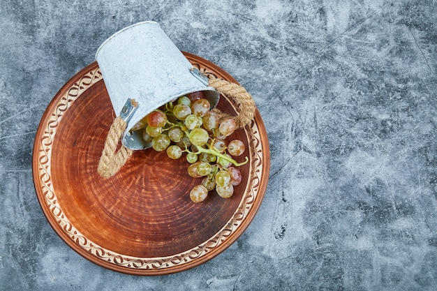 Small bucket of grapes inside ceramic plate on a marble background.