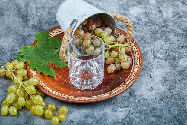 Small bucket of grapes onside ceramic plate and a glass on marble.