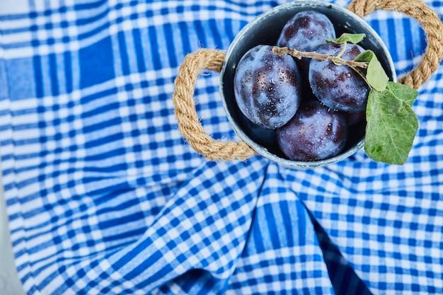 블루 식탁보에 정원 매의 작은 양동이.