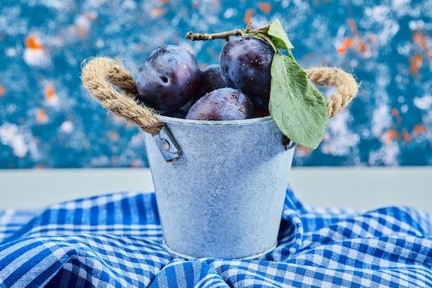 青いテーブルクロスに庭の梅の小さなバケツ。