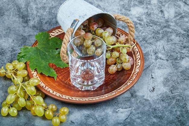 Небольшое ведро с виноградом внутри керамической тарелки и стакана на мраморном фоне. фото высокого качества