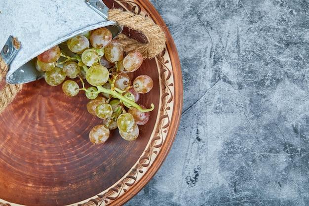 Небольшое ведерко с виноградом на керамической тарелке на мраморе.