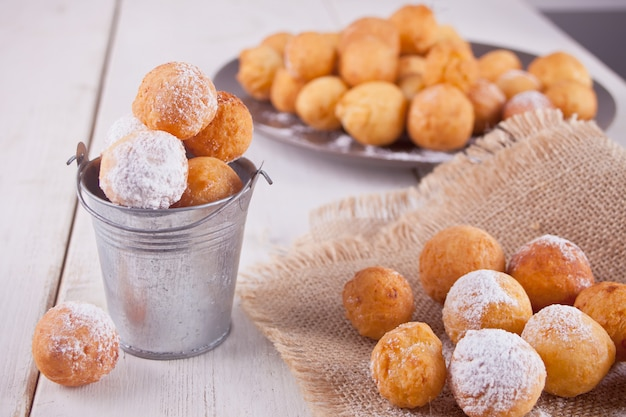 Small bucket and plate with small balls of freshly baked homemade cottage cheese doughnuts