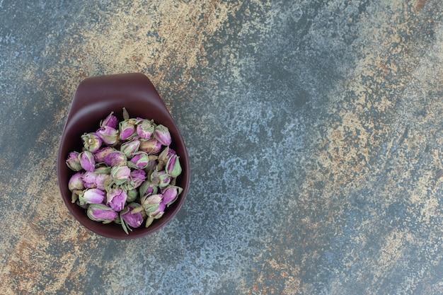 Small budding roses in dark bowl.