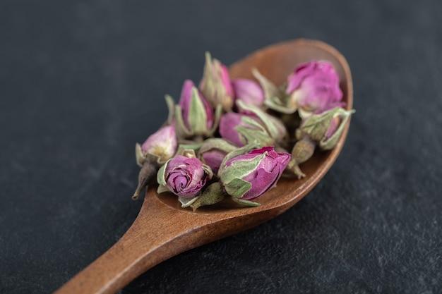Piccole rose in erba sul cucchiaio di legno.