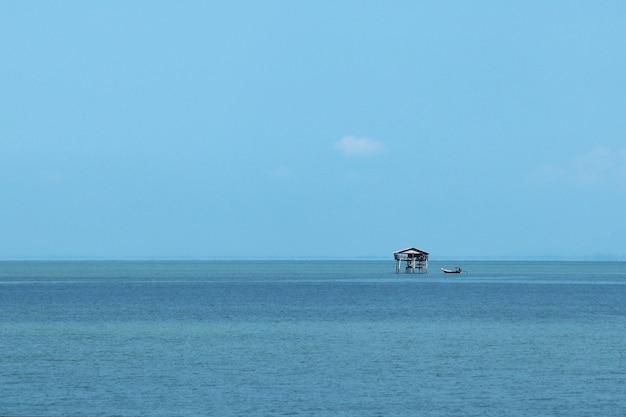 낮에는 햇빛과 푸른 하늘 아래 바다에 작은 건물