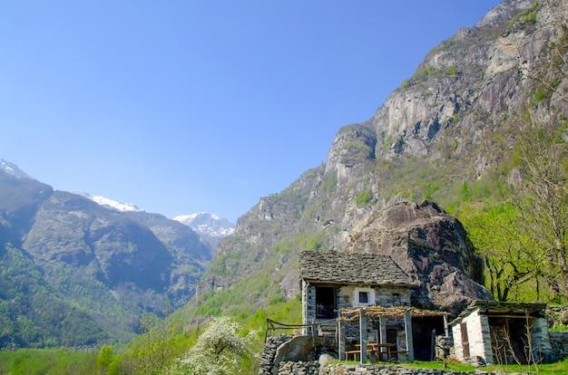スイスのティチーノ州の緑に覆われた岩に囲まれた山の小さな建物