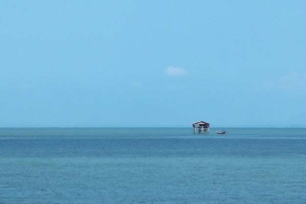 Piccolo edificio in mare sotto la luce del sole e un cielo azzurro di giorno