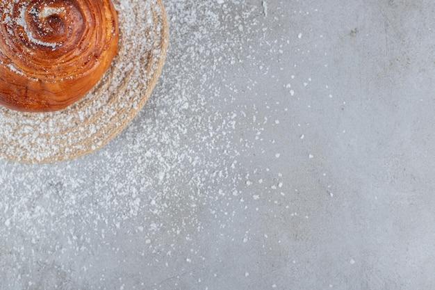 Маленькая булочка на подставке, покрытой кокосовой пудрой, на мраморном столе.