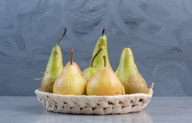 Small bundle of assorted pears in a white basket on marble background.