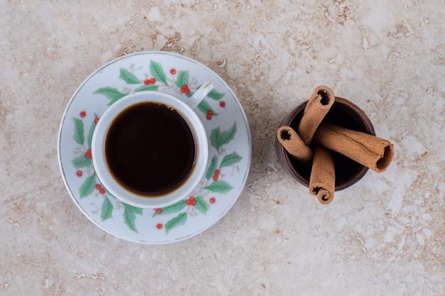 Un piccolo fascio di bastoncini di cannella e una tazza di caffè