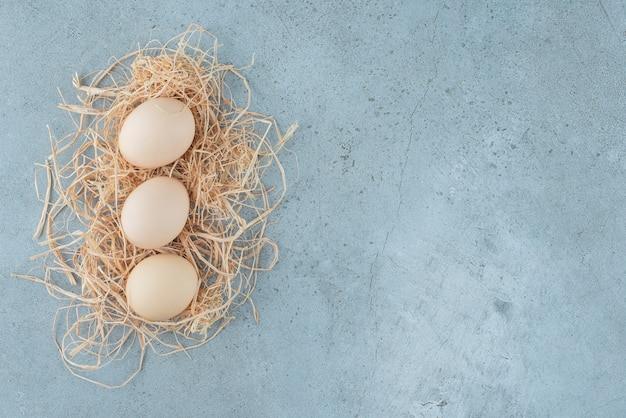 Small bundle of eggs on a small pile of straw on marble background. high quality photo
