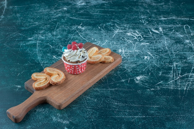 Small bundle of flaky cookies and a cupcake on a board on blue background. high quality photo