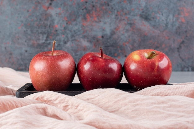 Small bundle of fresh apples on a tray on textile surface
