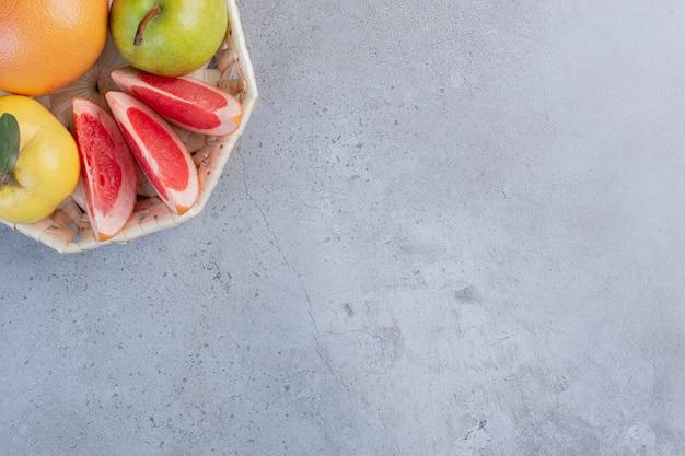 Un piccolo fascio di frutta in un cesto bianco su sfondo marmo.