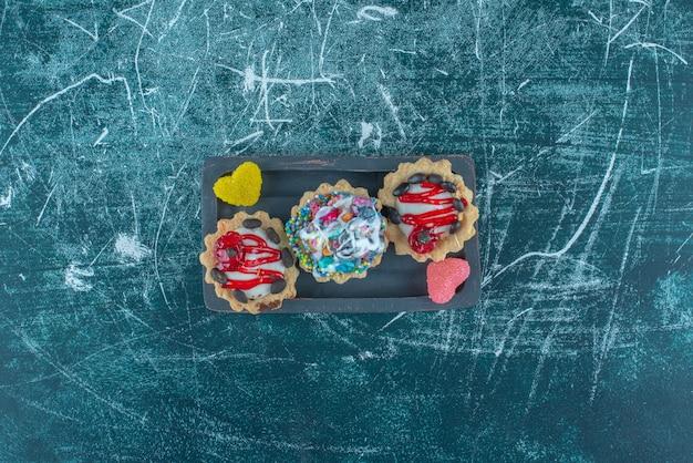 Небольшая пачка кексов и мармелад на блюде на синем фоне. фото высокого качества