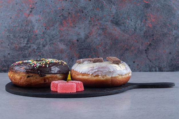 Небольшие связки мармеладов и два пончика на подносе на мраморной поверхности