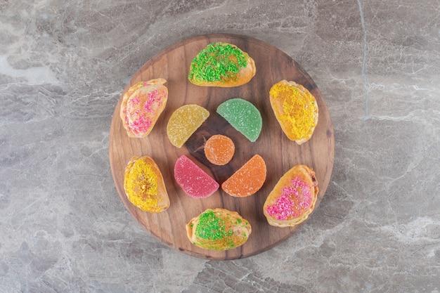 Маленькие булочки с различными начинками и желейные конфеты на доске на мраморной поверхности