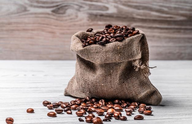 작은 삼 베 가방 전체 신선한 구운 된 아라비카 콩 및 일부 씨앗 거짓말 테이블. 밝은 표면에 갈색의 천연 로부스타 곡물이 든 자루.