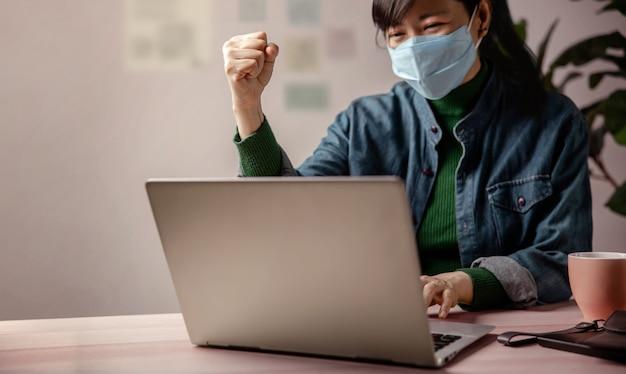 소기업 및 코로나 바이러스 개념 중 성공. 사업가 마스크를 쓰고 컴퓨터에서 작업