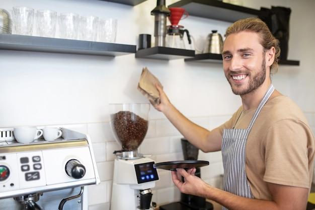 중소 기업, 카페. 그의 카페 요리에 커피 분쇄기 근처에 서 스트라이프 앞치마에 웃는 젊은 수염 난된 남자