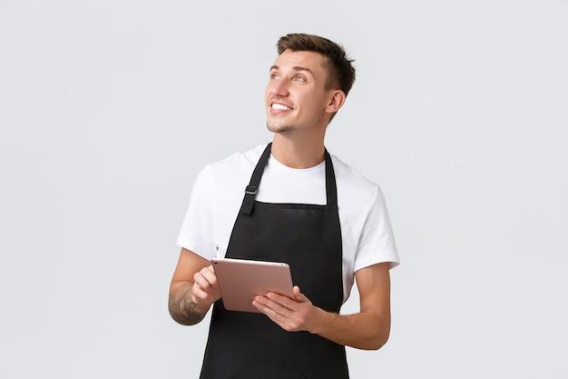 Маленькие бизнес-кафе и сотрудники кафе концепция дружелюбного харизматичного светловолосого парня-бариста или подождите ...