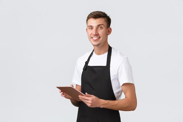 Концепция сотрудников кафе и кафе для малого бизнеса красивый официант-бариста в фартуке принимает ...