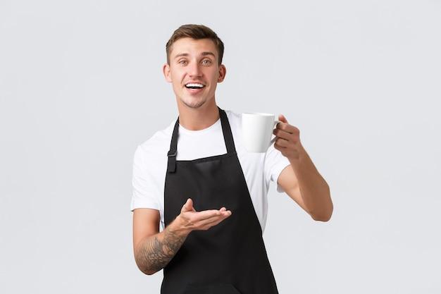 소규모 비즈니스 커피 숍 카페 및 레스토랑 개념 친절하고 잘 생긴 웨이터 바리스타가 음료수를 판매합니다.