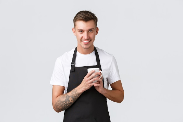 中小企業のコーヒーショップのカフェやレストランは、コーヒーホールドを楽しんでいるハンサムなバリスタをコンセプトにしています...