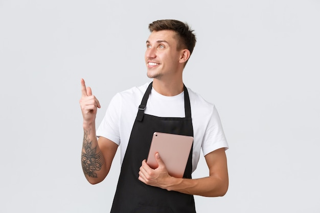 Small business coffee shop and cafe employees concept handsome friendly barista cafe owner in apron ...
