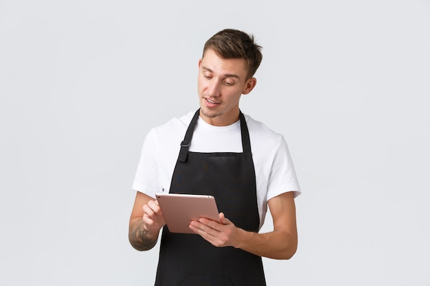 Small business coffee shop and cafe employees concept handsome young guy barista waiter taking order...