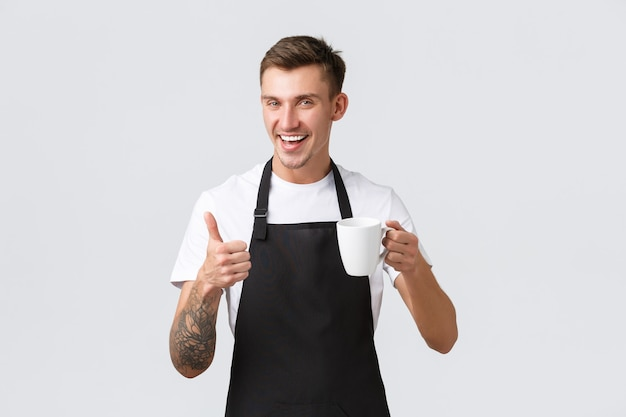 Small business coffee shop cafe and restaurants concept friendly handsome waiter barista selling drink handing cappuccino in mug guest smiling happy white wall recommend beverage