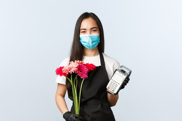 Small business, coronavirus pandemic, orders and shops concept. friendly smiling asian female employee in store, wear medical mask and gloves, holding bouquet order and pos terminal