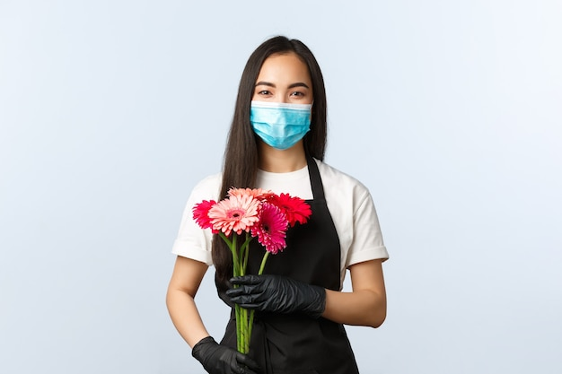 Small business, coronavirus pandemic, orders and shops concept. smiling cute asian female florist in medical mask, holding bouquet for customer, selling flowers during covid-19 outbreak.